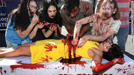 PETA (People for the Ethical Treatment of Animals) supporters dressed like zombies pretend to gorge themselves on a victim during a Halloween themed protest against consumption of animal meat in Hollywood, California, on October 26, 2017. The protest was to remind passersby that animals are made of flesh and blood like humans. / AFP PHOTO / Mark RALSTON        (Photo credit should read MARK RALSTON/AFP/Getty Images)