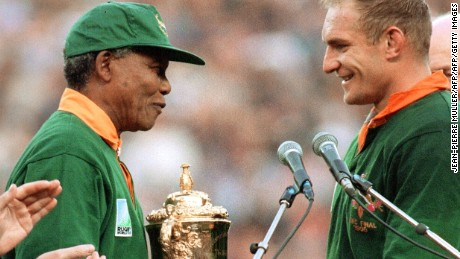 South Africa's president Nelson Mandela congratulates South Africa's rugby team captain Fran?ois Pienaar before handing him the William Webb trophy after his team's victory over New Zealand (15-12) in the final of the Rugby World Cup at Ellis Park in Johannesburg 24 June 1995. AFP/JEAN-PIERRE MULLER (Photo credit should read JEAN-PIERRE MULLER/AFP/Getty Images)