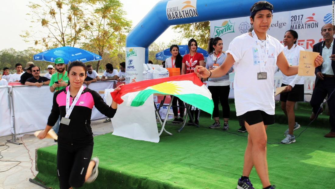 The first and third place winners of the women's race wave the Kurdish flag.