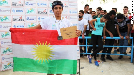Winner of the women's 10km race, Amal Khidir, takes photos with a Kurdish flag at the awards ceremony.