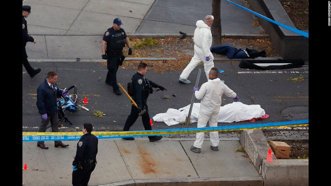 Police officers stand next to a body covered under a white sheet.