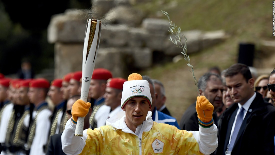 Greek cross-country skier Apostolos Angelis had the honor of being the first official torchbearer on this occasion. Here he also holds an olive tree branch as a symbol of peace.