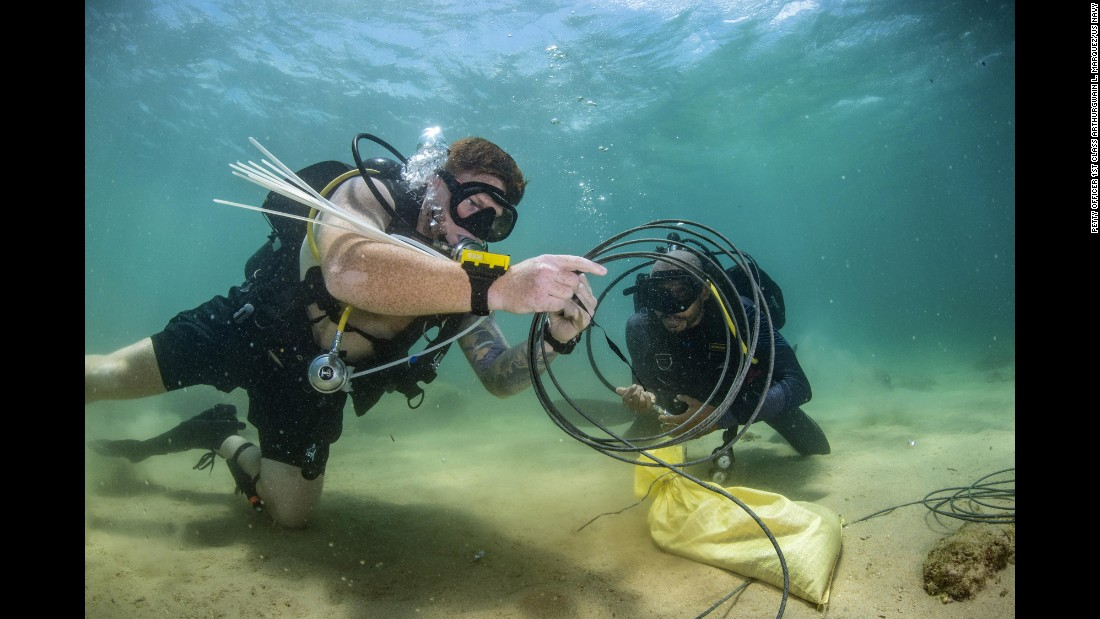 Navy Petty Officer 1st Class Daniel Lehne, left, and a Sri Lankan Navy diver conduct demolition operations during an underwater training exercise in Trincomalee, Sri Lanka, on Tuesday, October 3.