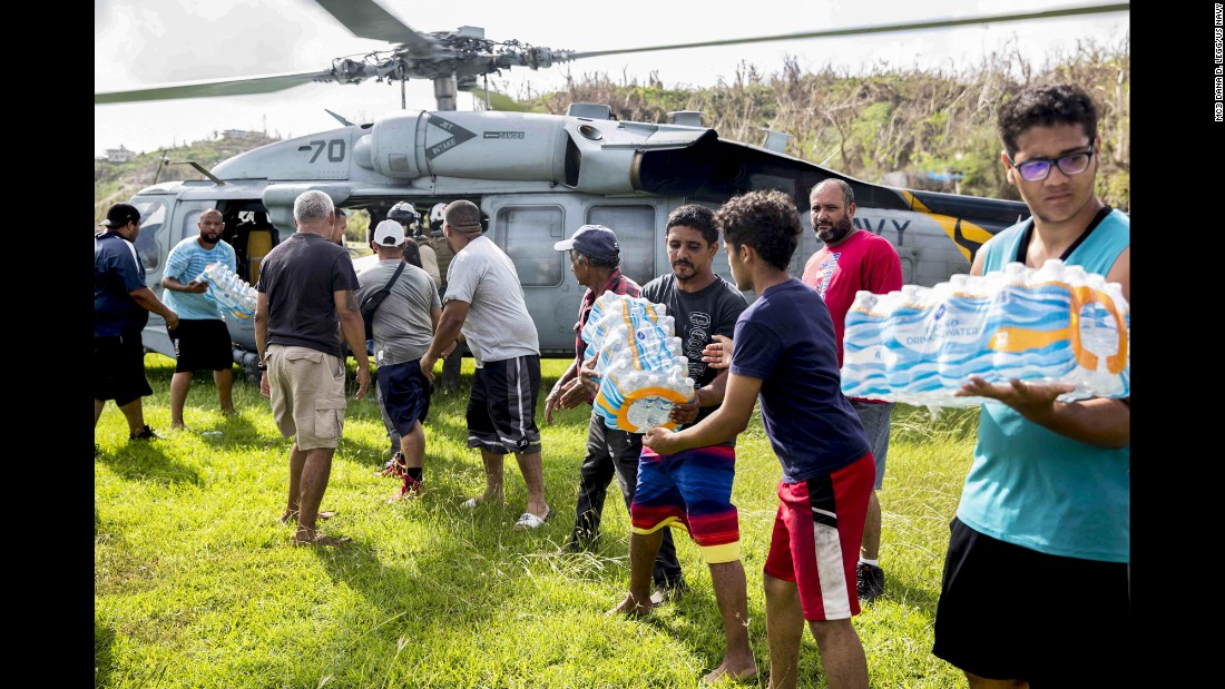 "US sailors and local volunteers unload drinking water from a military helicopter in Puerto Rico on Sunday, October 8. The sailors are assigned to the USS Kearsarge, which is helping with relief efforts in <a href=""http://www.cnn.com/interactive/2017/09/world/hurricane-maria-puerto-rico-cnnphotos/index.html"" target=""_blank"">the aftermath of Hurricane Maria.</a>"