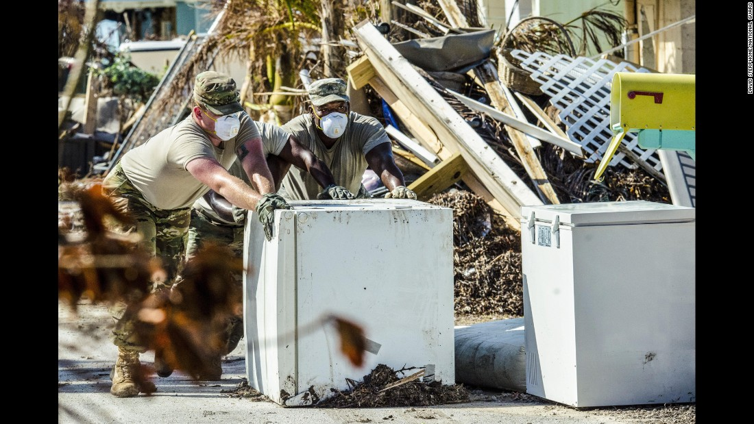 "Army Pfc. Cody Hughes, left, and Sgt. Robert Brown remove a refrigerator Tuesday, October 3, from a Marathon, Florida, home that was devastated by <a href=""http://www.cnn.com/2017/09/10/us/gallery/hurricane-irma-florida/index.html"" target=""_blank"">Hurricane Irma.</a>"