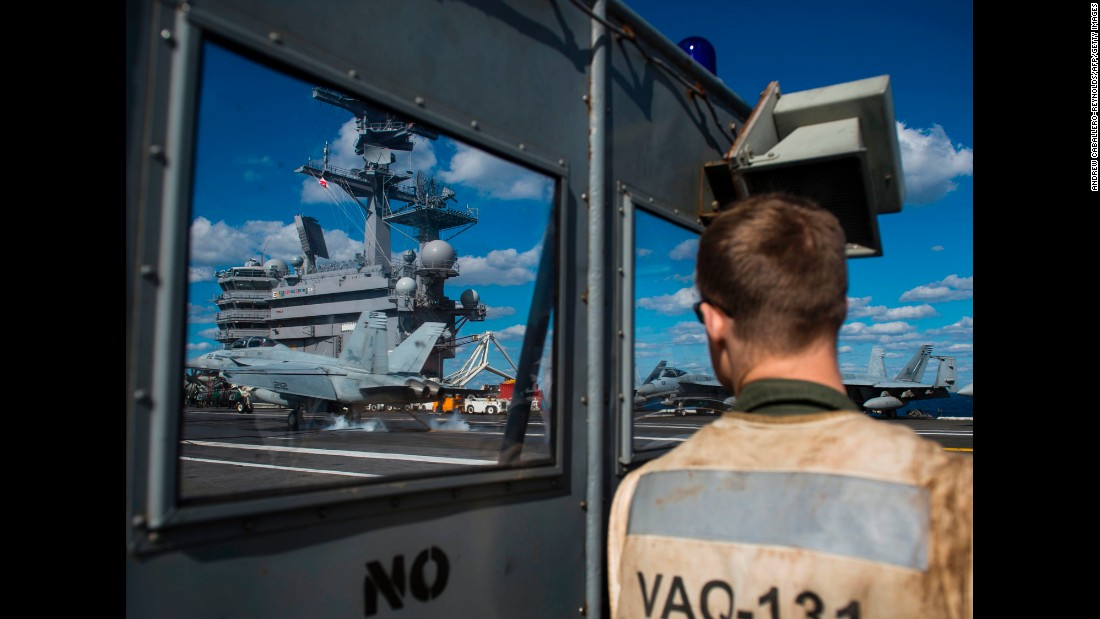 A service member watches a jet land on the USS George H.W. Bush, an aircraft carrier in the Atlantic Ocean on Thursday, October 26. The aircraft carrier was taking part in Operation Bold Alligator, a multinational training exercise.