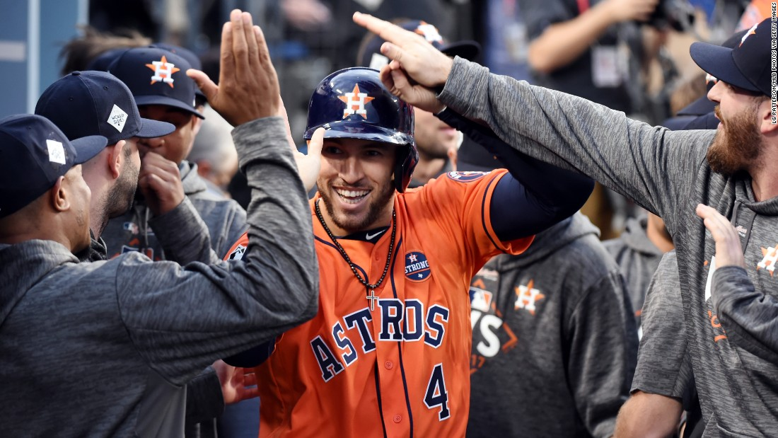 Springer is greeted in the dugout after scoring a run in the first inning. He opened the game with a double.
