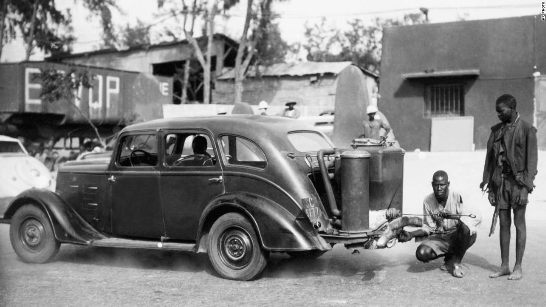 "When gasoline imports ceased in Senegal in the 1940s, people had to improvise. Pictured here are two Senegalese men stoking a charcoal-burning automobile called the ""Gas-o-gene"" in 1942. <br />"