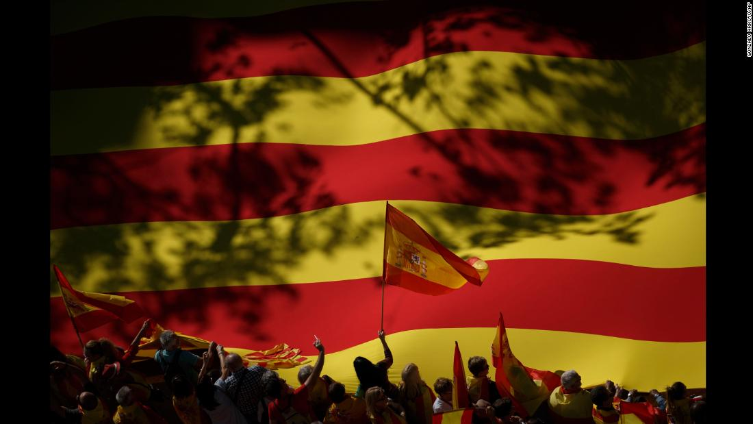 "An activist waves a Spanish flag in front of a giant Catalan flag during a mass rally in Barcelona, Spain, on Sunday, October 29. <a href=""http://www.cnn.com/2017/10/29/europe/catalonia-independence-spain/index.html"" target=""_blank"">Hundreds of thousands of people gathered</a> to protest Catalonia's declaration of independence."