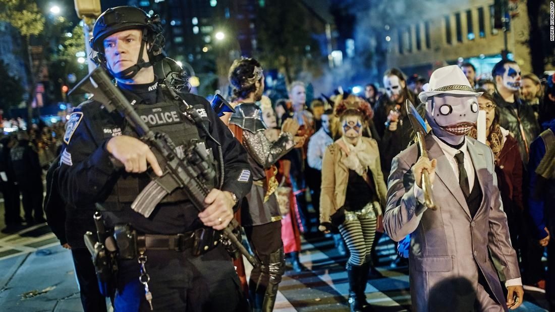 Armed police stand guard in New York City as revelers march during the Greenwich Village Halloween Parade on Tuesday, October 31.