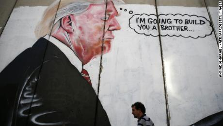 A Palestinian man walks past graffiti depicting US President Donald Trump on the controversial Israeli separation wall in the West Bank town of Bethlehem, on August 7, 2017. / AFP PHOTO / AHMAD GHARABLI        (Photo credit should read AHMAD GHARABLI/AFP/Getty Images)