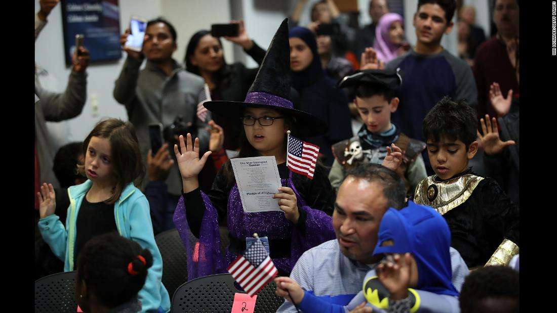 Children from 22 countries take the oath of US citizenship during a Halloween-themed ceremony in Fairfax, Virginia, on Tuesday, October 31.