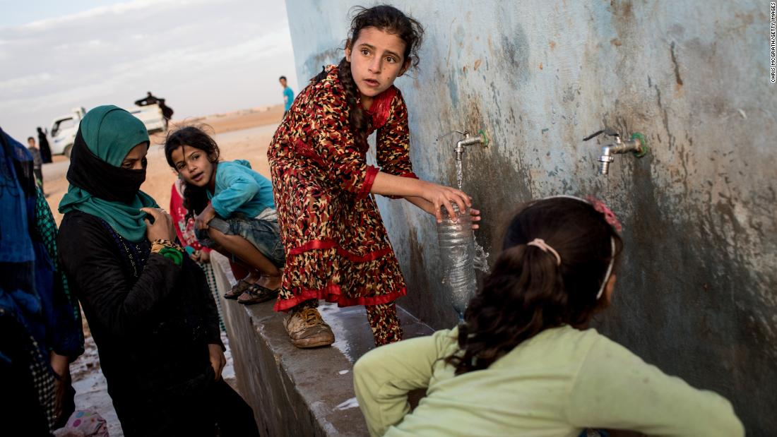 A girl fills a bottle at a water pump station for internally displaced people in Ain Issa, Syria, on Sunday, October 29.