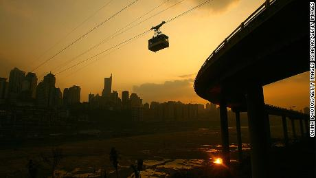 "CHONGQING, CHINA - DECEMBER 12: (CHINA OUT) A cable car runs along the Chongqing Jialing River Ropeway with the residential buildings in the background, at sunset on December 12, 2007 in Chongqing Municipality, China. Chongqing reported about 170 ""blue sky days"" this year, 70 days more than last year. (Photo by China Photos/Getty Images)"
