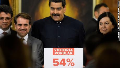 "Venezuelan President Nicolas Maduro (C) holds a sign that reads ""popular victory 54 percent; we are happiness, we are the majority"" after a press conference with international media correspondents at the Miraflores Presidential Palace in Caracas on October 17, 2017. / AFP PHOTO / FEDERICO PARRA        (Photo credit should read FEDERICO PARRA/AFP/Getty Images)"
