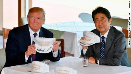 US President Donald Trump (L) and Japanese Prime Minister Shinzo Abe pose after they signed hats reading 'Donald and Shinzo, Make Alliance Even Greater' at the Kasumigaseki Country Club in Kawagoe, near Tokyo on November 5, 2017.  Trump touched down in Japan, kicking off the first leg of a high-stakes Asia tour set to be dominated by soaring tensions with nuclear-armed North Korea. / AFP PHOTO / POOL / FRANCK ROBICHON        (Photo credit should read FRANCK ROBICHON/AFP/Getty Images)