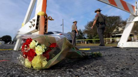 A bouquet of flowers lies near where law enforcement officials work outside First Baptist Church in Sutherland Springs.