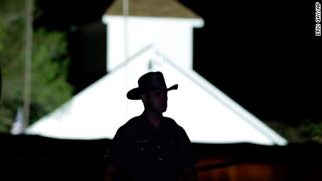 A law enforcement official walks past the First Baptist Church of Sutherland Springs, the scene of a mass shooting, Sunday, Nov. 5, 2017, in Sutherland Springs, Texas. (AP Photo/Eric Gay)