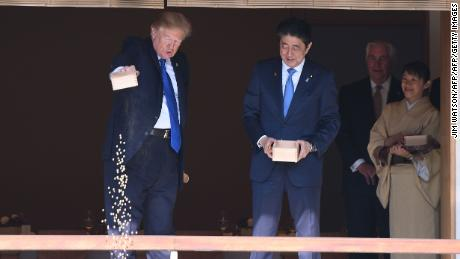 US President Donald Trump (C) feeds koi fish as Japanese Prime Minister Shinzo Abe (R)looks on during a welcoming ceremony in Tokyo on November 6, 2017.