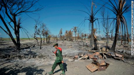 PAUKTAW, MYANMAR - OCTOBER 27: A soldier stands guard at quarter No.3 in Pauktaw township, that was burned in recent violence between Buddhist Rakhine and Muslim Rohingya, on October 27, 2012 in Pauktaw,  Myanmar.  Over twenty thousand people have been left displaced following violent clashes which has so far claimed a reported 80 lives. Clashes between Rakhine people, who make up the majority of the state's population, and Muslims  from the state of  Rohingya began in June. (Photo by Kaung Htet/Getty Images)