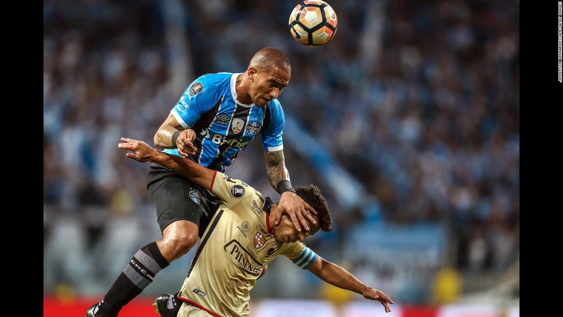 Gremio midfielder Jailson jumps over Barcelona's Matias Oyola during a Libertadores Cup match in Porto Alegre, Brazil, on Wednesday, November 1.