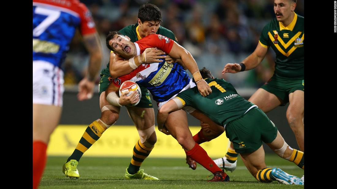 France's Benjamin Garcia is tackled by Australian players during a Rugby League World Cup match on Friday, November 3.