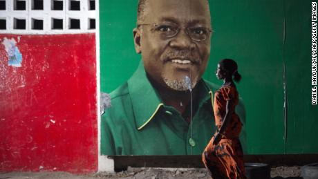 A woman walks past an election billboard of candidate John Magufuli.