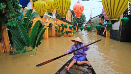 Nguyen Thi Vui paddles her boat in the flooded streets of Hoi An in central Vietnam on Monday, Nov. 6, 2017.