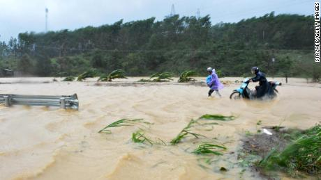 People walk through floodwaters on a highway in the central province of Dak Lak brought by Typhoon Damrey on Saturday.