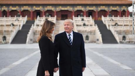 US President Donald Trump holds hands with First Lady Melania Trump in the Forbidden City in Beijing on November 8, 2017.