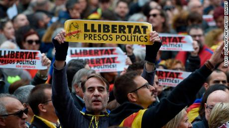 "People hold placards reading ""Free political prisoners"" and Catalan pro-independence 'Estelada' flags during a demonstration outside the Generalitat Palace in Barcelona on November 8, 2017 during a regionwide strike called by a pro-independence union. Protesters blocked roads, highways and train tracks in Catalonia as part of a region-wide strike called by a pro-independence union.   / AFP PHOTO / LLUIS GENE        (Photo credit should read LLUIS GENE/AFP/Getty Images)"