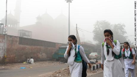 Indian schoolchildren cover their faces as they walk to school, November 8, 2017. Delhi has since mandated the closure of all schools until the pollution clears.