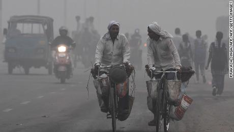 Indian commuters drive amid heavy smog in New Delhi on November 7, 2017. New Delhi woke up to a choking blanket of smog on November 7 as air quality in the world's most polluted capital city reached hazardous levels. The US embassy website said levels of the fine pollutants known as PM2.5 that are most harmful to health reached 703 -- well over double the threshold of 300 which authorities class as hazardous.   / AFP PHOTO / PRAKASH SINGH        (Photo credit should read PRAKASH SINGH/AFP/Getty Images)