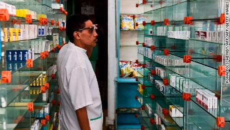 A worker of an empty pharmacy is pictured in Caracas on May 30, 2016. The shortage of medicines in Venezuela exceeds 85%, revealed the president of the farmaceutical federation of Venezuela, Freddy Ceballos. / AFP / RONALDO SCHEMIDT        (Photo credit should read RONALDO SCHEMIDT/AFP/Getty Images)