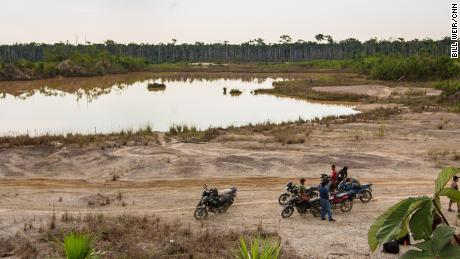 "A group of motorcycle taxis known as ""Los Tigres"" stops near a toxic mining site in the Peruvian Amazon."