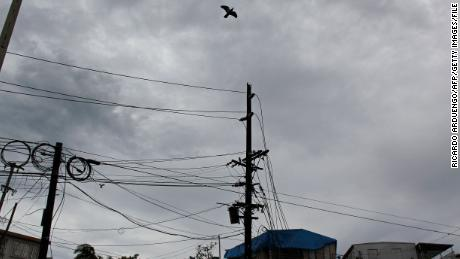 "Damaged power line poles are seen in front of houses affected by the passing of Hurricane Maria in San Juan, Puerto Rico on November 7, 2017.  The Center for Puerto Rican Studies at Hunter College in New York estimated in a report released last month that about 114,000 to 213,000 Puerto Rican residents will leave the island annually ""as a result of Hurricane Maria."" / AFP PHOTO / Ricardo ARDUENGORICARDO ARDUENGO/AFP/Getty Images"