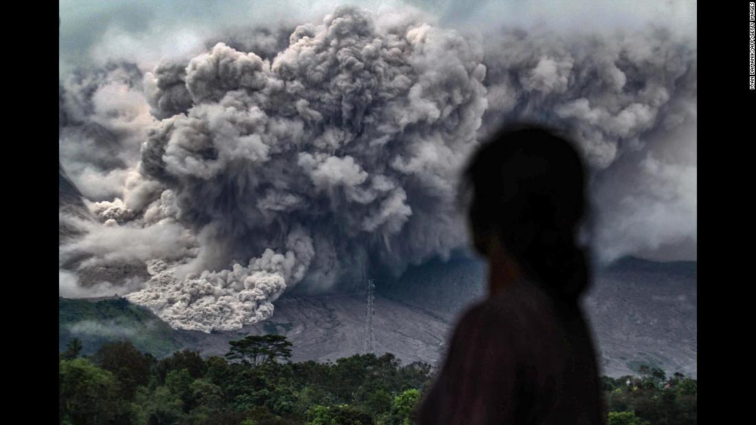 A woman watches Mount Sinabung erupt in Karo, Indonesia, on Friday, November 3. The volcano has been highly active since 2010.