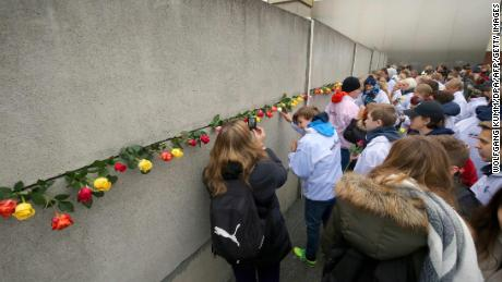 Jewish youth place roses in a crack at the Berlin Wall Memorial on November 9, 2017 during the commemorations to mark the 28th anniversary of the fall of the Berlin Wall. / AFP PHOTO / DPA / Wolfgang Kumm / Germany OUTWOLFGANG KUMM/AFP/Getty Images