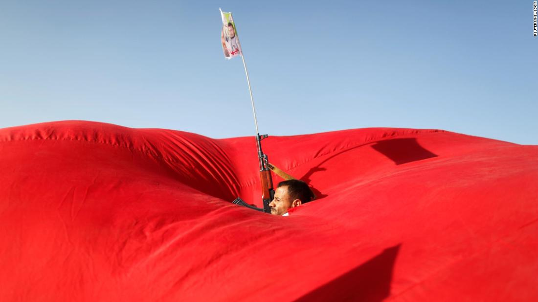 A man is seen in the gap of a flag as he attends a pro-Palestinian rally in Sanaa, Yemen, on Monday, November 6.