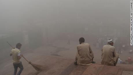 Indian visitors sit on the steps outside Jama Masjid amid heavy smog in the old quarters of New Delhi on November 8, 2017. Delhi shut all primary schools on November 8 as pollution levels hit nearly 30 times the World Health Organization safe level, prompting doctors in the Indian capital to warn of a public health emergency. Dense grey smog shrouded the roads of the world's most polluted capital, where many pedestrians and bikers wore masks or covered their mouths with handkerchiefs and scarves.  / AFP PHOTO / Sajjad HUSSAIN        (Photo credit should read SAJJAD HUSSAIN/AFP/Getty Images)