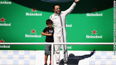 Felipe Massa, alongside son Felipinho, waves to the home fans after his final F1 race at Interlagos.