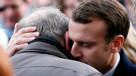 French President Emmanuel Macron hugs a relative of a victim at the Bataclan concert hall during a ceremony Monday.