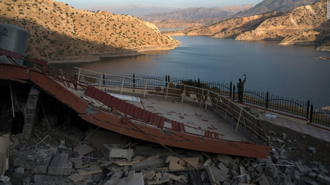 A man takes a picture of a destroyed structure near Iraq's Darbandikhan Lake on November 13.