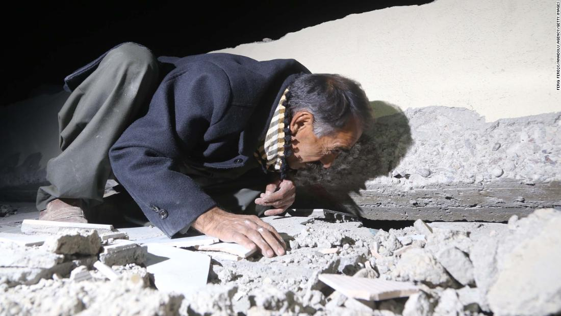 A man searches for people trapped in the rubble in Iraq's Darbandikhan district on Sunday, November 12.
