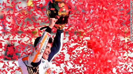 TOPSHOT - Repsol Honda Team's Spanish rider Marc Marquez celebrates after the MotoGP race of the Valencia Grand Prix at Ricardo Tormo racetrack in Cheste, near Valencia on November 12, 2017.  Spain's Marc Marquez sealed his sixth world championship and fourth in the premier MotoGP category with third place at the Valencia Grand Prix. Marquez's Honda teammate Dani Pedrosa won the race from France's Johann Zarco in second.  / AFP PHOTO / JOSE JORDAN        (Photo credit should read JOSE JORDAN/AFP/Getty Images)