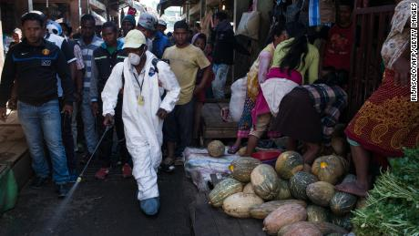 People stand back as a council worker sprays disinfectant during the clean-up of the market of Anosibe in the Anosibe district, one of the most unsalubrious districts of Antananarivo on October 10, 2017. The World Health Organization has warned that a deadly outbreak of the plague, which began in late August, has claimed more than 20 lives in Madagascar and is swiftly spreading in cities across the country. Rats are porters of fleas which spread the bubonic plague and are attracted by garbages and unsalubrity. Pneumonic plague, which is passed through person-to-person transmission, has also been recorded. / AFP PHOTO / RIJASOLO        (Photo credit should read RIJASOLO/AFP/Getty Images)