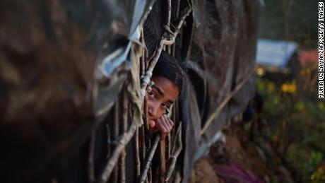 A Rohingya girl looks out from a makeshift shelter in the Bangladeshi district of Ukhia.