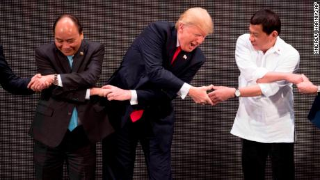 "U.S. President Donald Trump, center, reacts as he does the ""ASEAN-way handshake"" with Vietnamese Prime Minister Nguyen Xuan Phuc, left, and Philippine President Rodrigo Duterte on stage during the opening ceremony at the ASEAN Summit at the Cultural Center of the Philippines, Monday, Nov. 13, 2017, in Manila, Philippines. Trump initially did the handshake incorrectly. Trump is on a five-country trip through Asia traveling to Japan, South Korea, China, Vietnam and the Philippines. (AP Photo/Andrew Harnik)"
