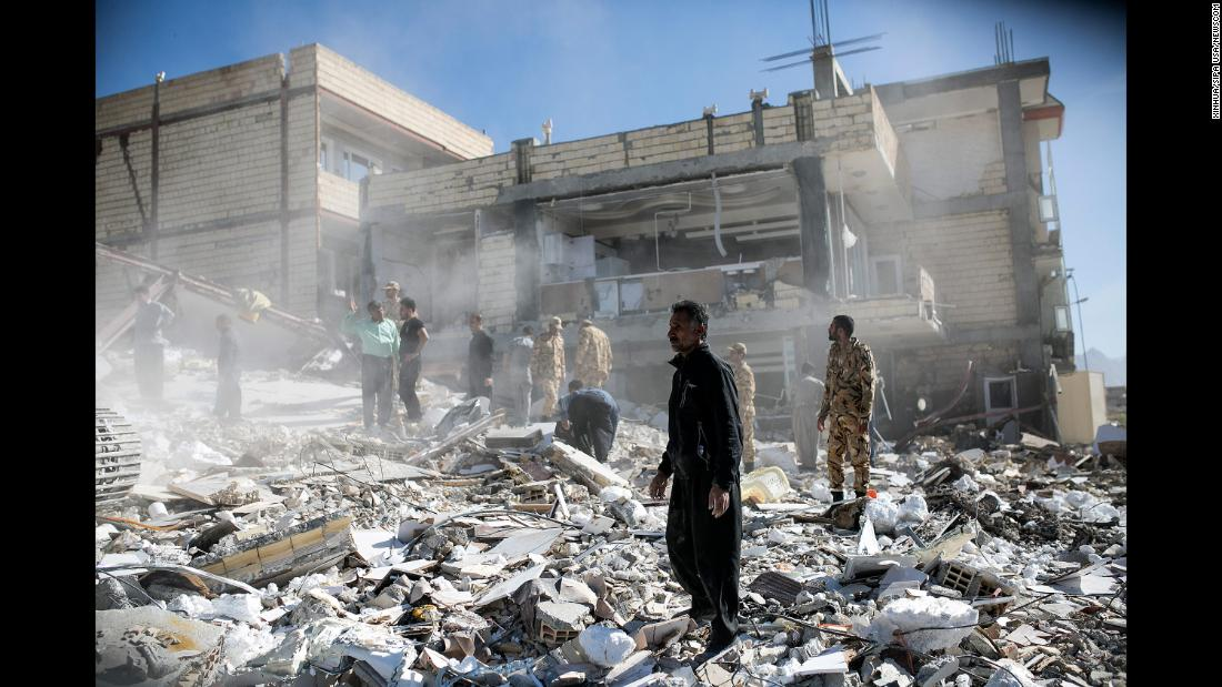 People walk through rubble in Sarpol-e Zahab on November 13.