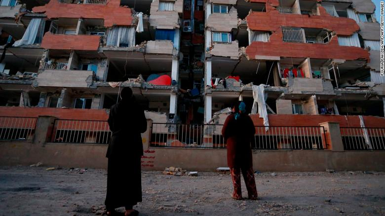 People look up at a damaged residential building in Sarpol-e Zahab, Kermanshah province.